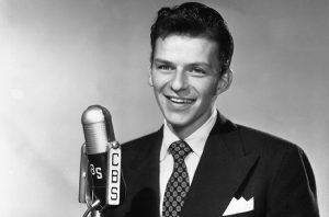 20th October 1942:  American singer and actor Frank Sinatra (1915-1998) standing in front of a CBS microphone and smiling, in a promotional portrait for his radio show.  (Photo by CBS Photo Archive/Getty Images)